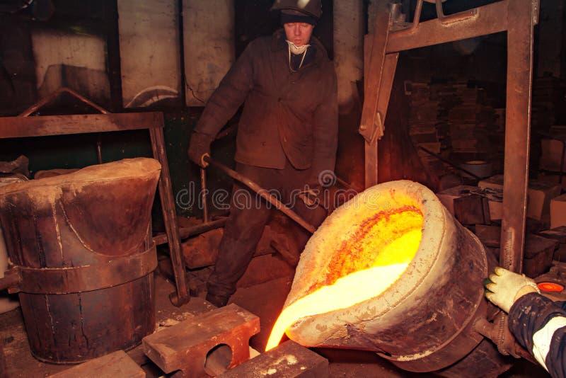 Ryssland Ryazan 14 Februari 2019 - arbetaren förhindrar smält metall med en stång i fabrik av metallrollbesättningprocessen royaltyfri fotografi