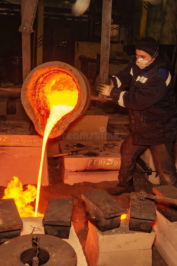 Ryssland Ryazan 14 Februari 2019 - arbetaren häller kvarlevor av smält metall i fabrik av metallrollbesättningprocessen royaltyfri foto