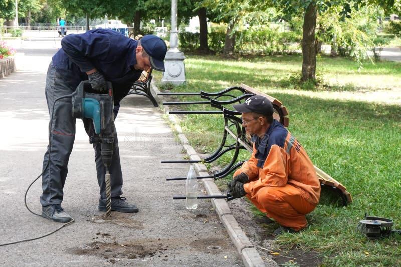 Ryssland stad av Magnitogorsk, - Augusti, 19, 2015 Arbetare monterar anti--vandalen som bänkar i en stad parkerar arkivbilder