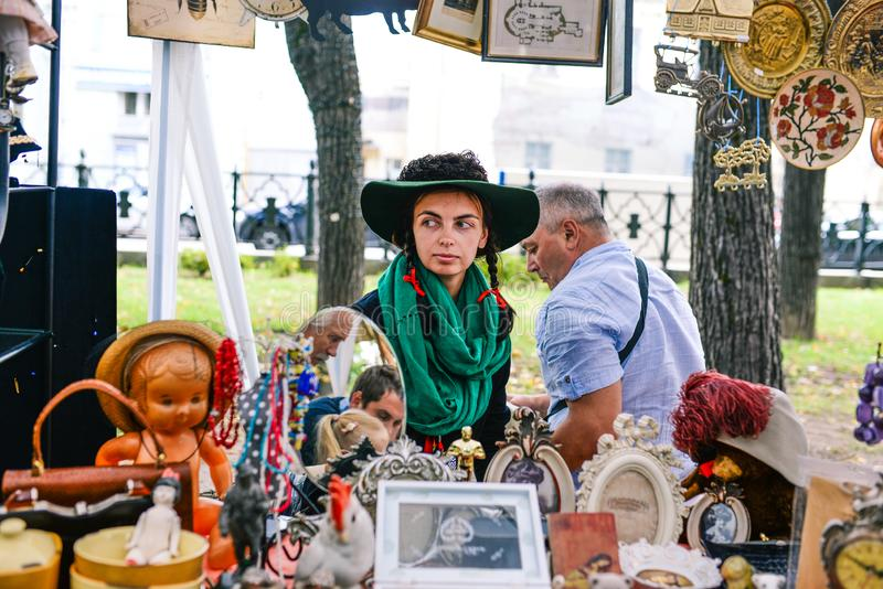 Ryssland stadsMoskva - September 6, 2014: Ung härlig flicka i en hatt med paly och grön halsduk En kvinna säljer antikviteter i a arkivbild
