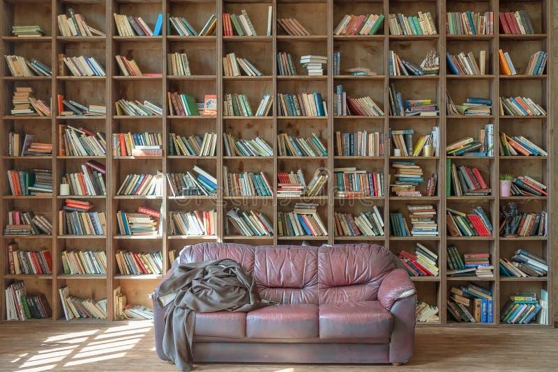 Ryssland Tatarstan, April 20, 2019 gammalt arkiv Enorm bokhylla med böcker Solen skiner fr?n f?nstret Gammal soffa på arkivbilder