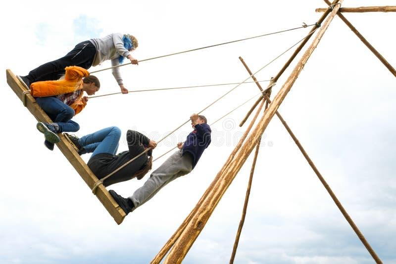 Ryssland Tyumen, 15 06 2019 Barn av olik åldrar och gunga på de stora gammalmodiga trägungorna, mot den blåa himlen med arkivfoton