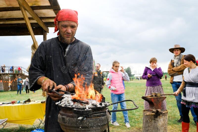 Ryssland Tyumen, 15 06 2019 Hovslagaren rymmer en mästarklass på att förfalska på festivalen av olika nationer Värmer järnet på arkivbilder