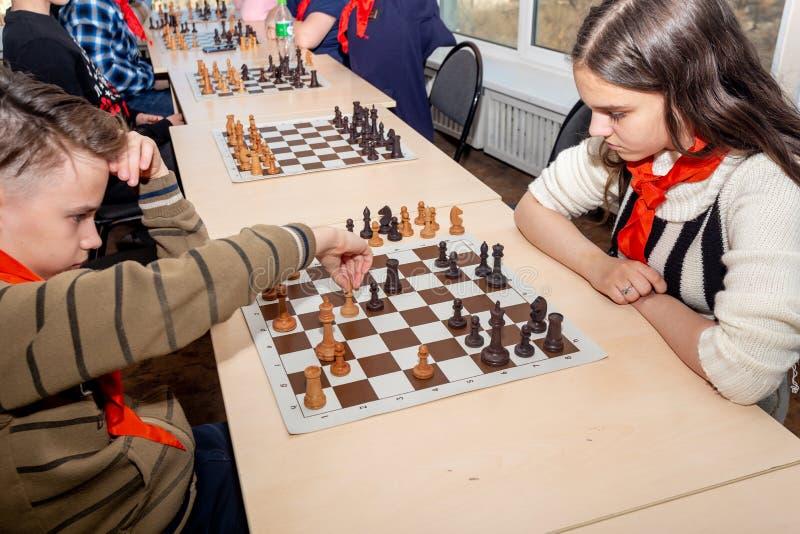 Ryssland Vladivostok, 12/01/2018 Ungar spelar schack under schackkonkurrens i schackklubba Utbildnings-, schack- och meningslekar royaltyfri bild