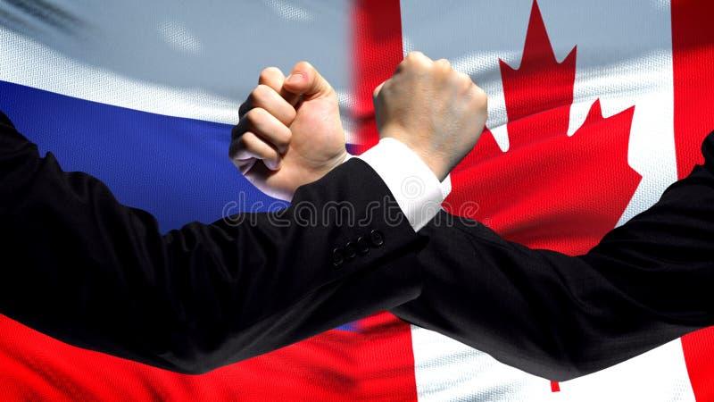 Ryssland vs Kanada konfrontation, landsmotsättning, nävar på flaggabakgrund arkivbild