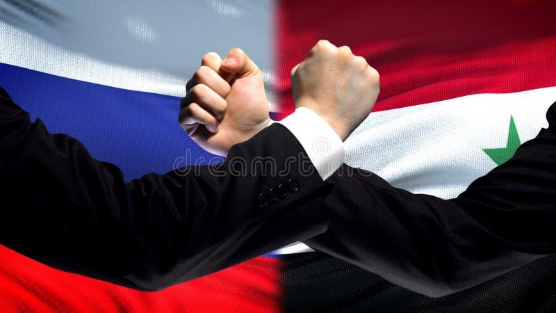Ryssland vs Syrien konfrontation, landsmotsättning, nävar på flaggabakgrund royaltyfri bild