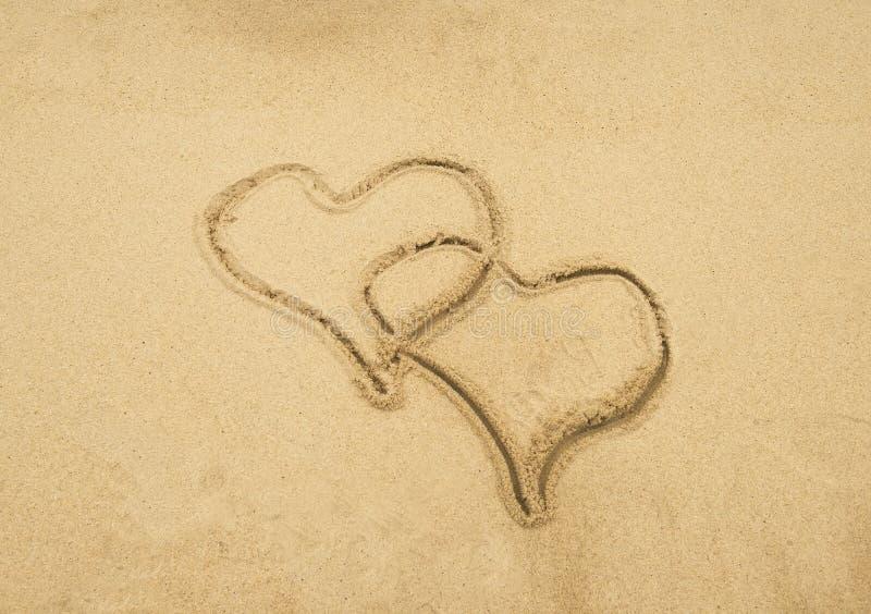 Rysującego w plaży dwa serca zdjęcie stock