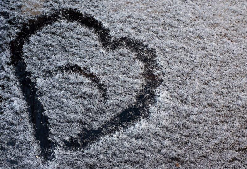 Rysunek w postaci serca na spadać śniegu na samochodowym szkle zdjęcia royalty free