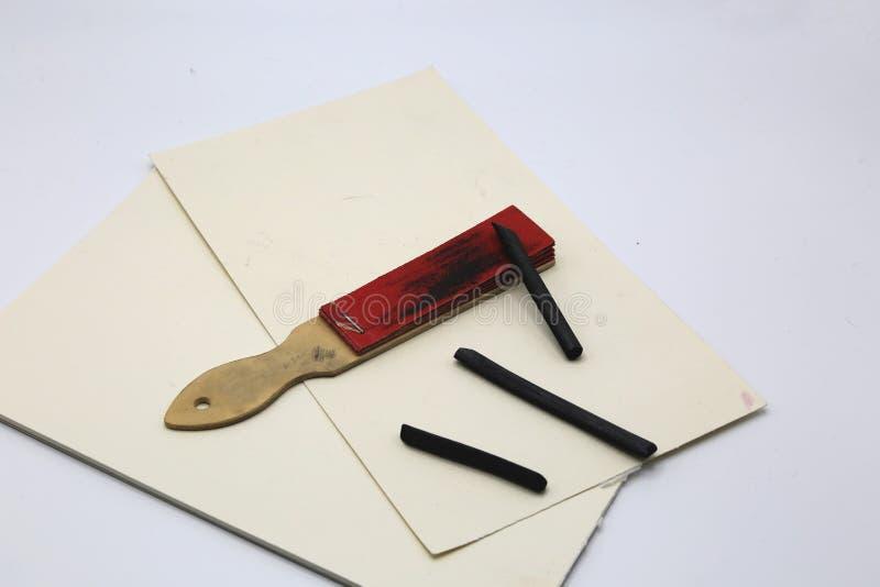 Rysunkowy węgiel drzewny, ścierny papier dla ostrzyć i papier, ciąć na arkusze z few linie w węglu drzewnym obrazy stock
