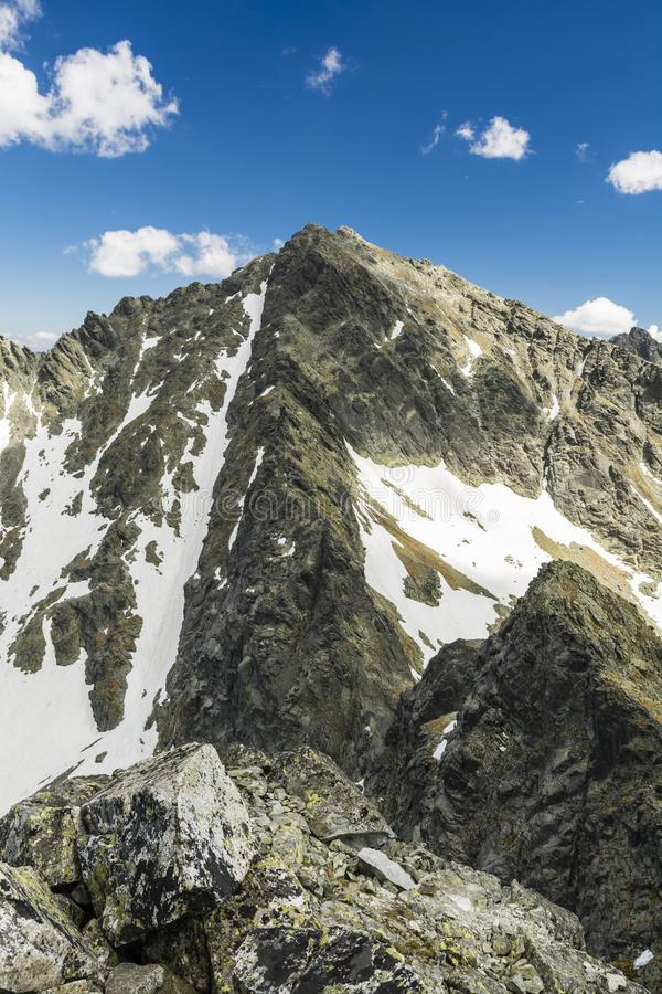 Rysy - a mountain peak in the High Tatras on the border between Poland and Slovakia. A popular destination for mountain tours. There is snow in the gully stock photo