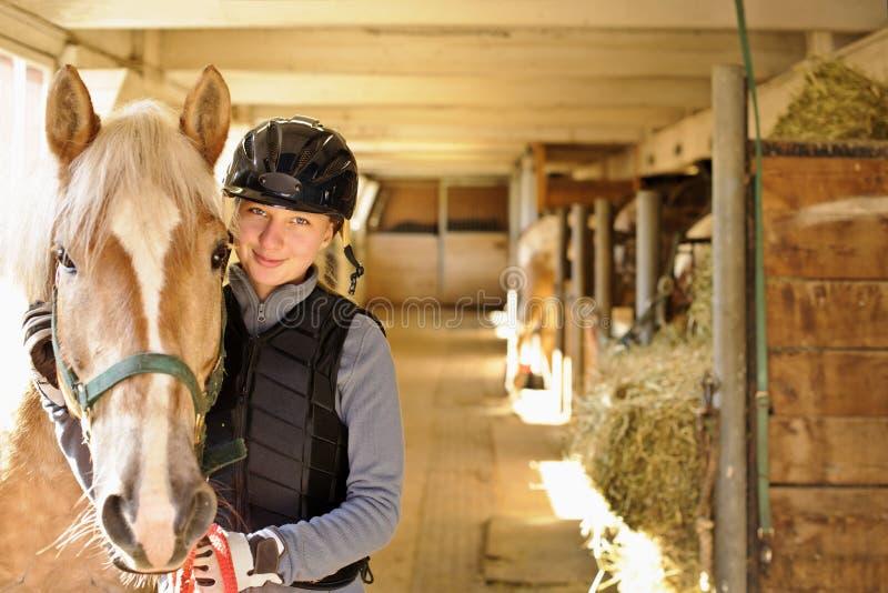 Ryttare med hästen i stall royaltyfri bild