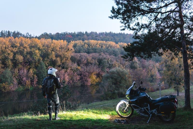 Ryttareanseendet med aff?rsf?retagmotorcykeln, motorcyklist, en mopedchauff?r ser, billyktor p?, nattskogen, naturlandskap royaltyfri bild