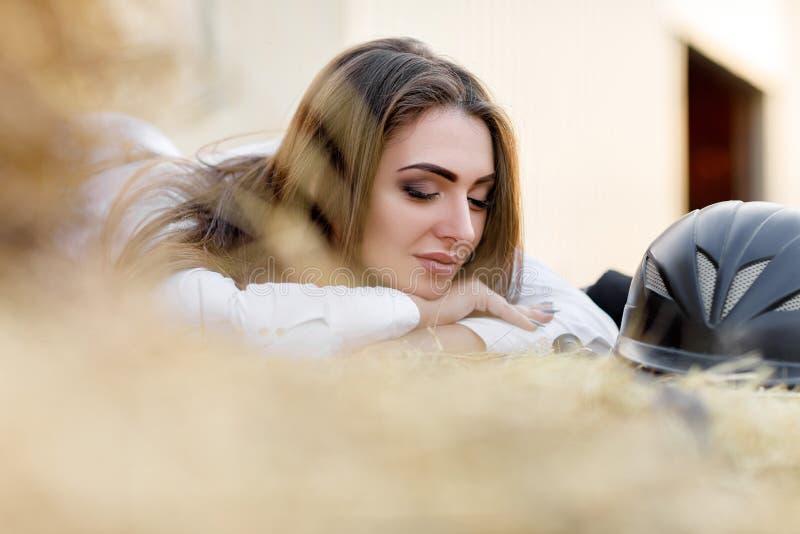Ryttaren som kvinnan med piskar, sitter på hö royaltyfri fotografi