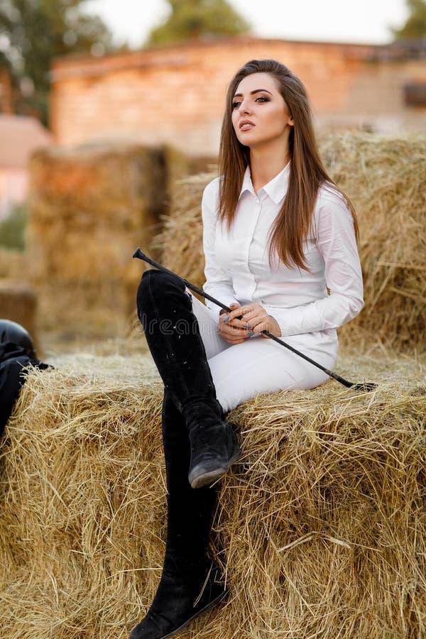Ryttaren som kvinnan med piskar, sitter på hö arkivfoton