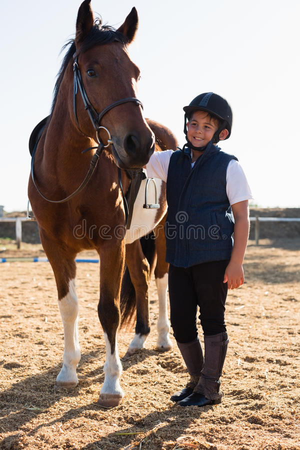 Ryttarepojke som smeker en häst i ranchen fotografering för bildbyråer
