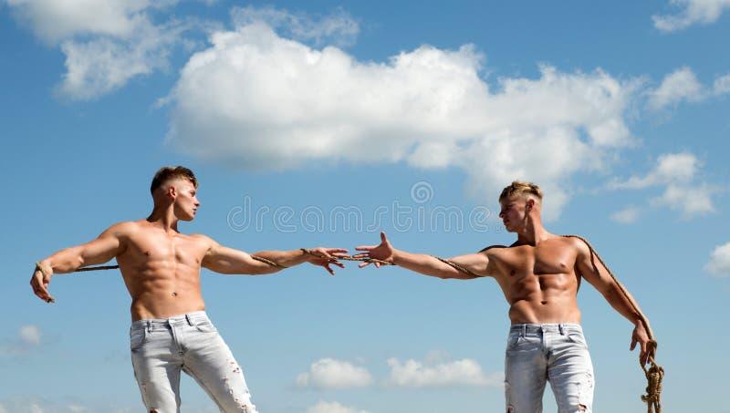 Rywalizować zwycięstwo Silnych mężczyzn ciągnienia arkana z mięśniową ręki siłą Mężczyźni pokazują daleko ich siłę przeciw zdjęcie stock
