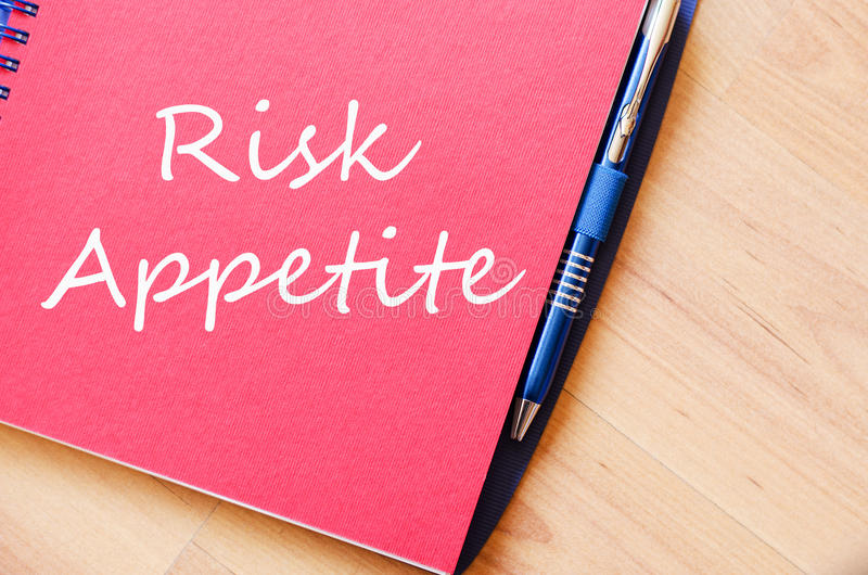 Ryzyko apetyt pisze na notatniku obraz stock