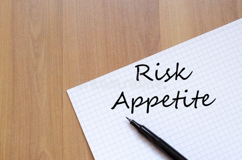 Ryzyko apetyt pisze na notatniku obrazy stock
