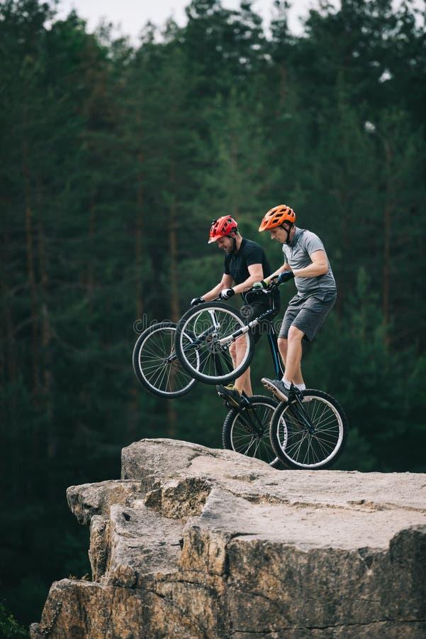 ryzykowni próbni rowerzyści stoi na tylnych kołach na skalistej falezie z zamazanym sosnowym lasem obraz royalty free