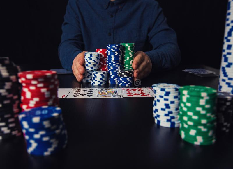 Ryzykowny faceta grzebaka gracz iść w pchać jego wielką stertę układy scaleni naprzód, zakłada się przy kasynowym hazardu stołem  obraz royalty free