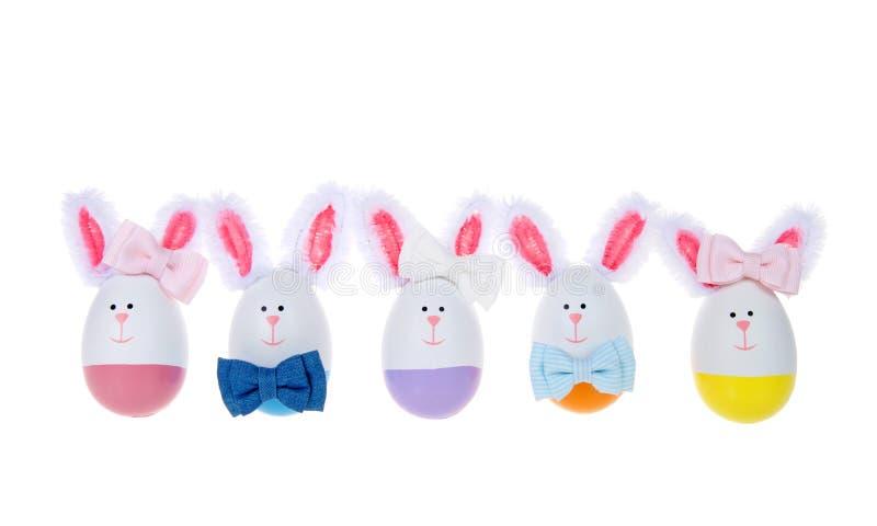 Rząd Wielkanocni jajka wykonywał ręcznie w króliki chłopiec i dziewczyny jest ubranym łęków krawaty odizolowywających, zdjęcia stock