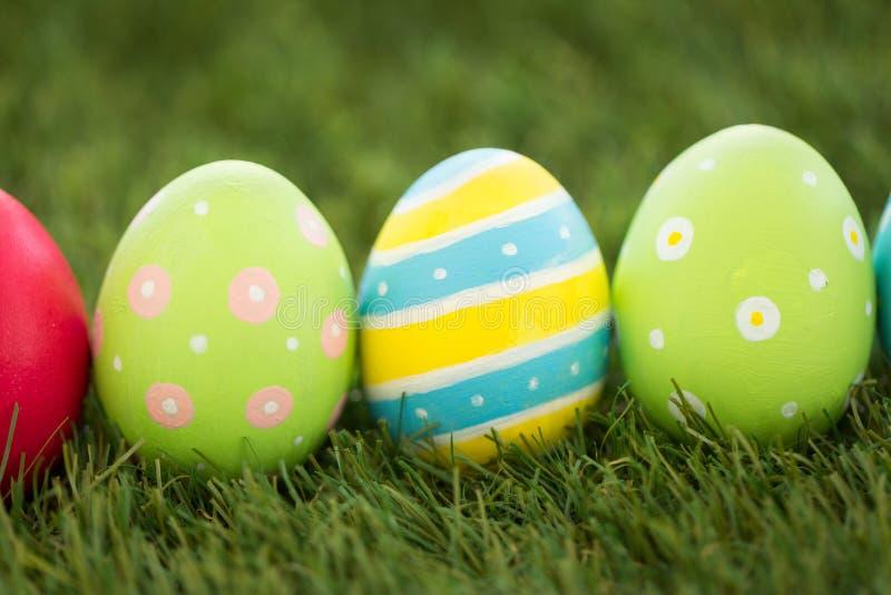 Rząd barwioni Easter jajka na sztucznej trawie zdjęcie stock