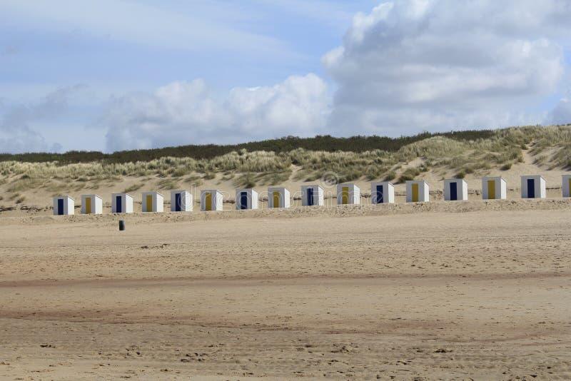 Rząd biali plażowi domy z żółtymi i błękitnymi drzwiami przed diunami z plażową trawą w cadzand, Holland obrazy royalty free