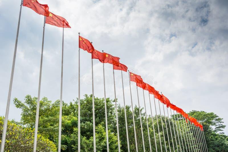 Rząd Chińska flaga państowowa podnosi w górę flagpole przeciw chmurnemu niebu w parku zdjęcia stock