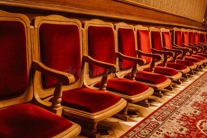 Rząd drewniani roczników krzesła zakrywający w czerwonym aksamita stojaku przeciw ścianie Hall w teatrze obrazy royalty free
