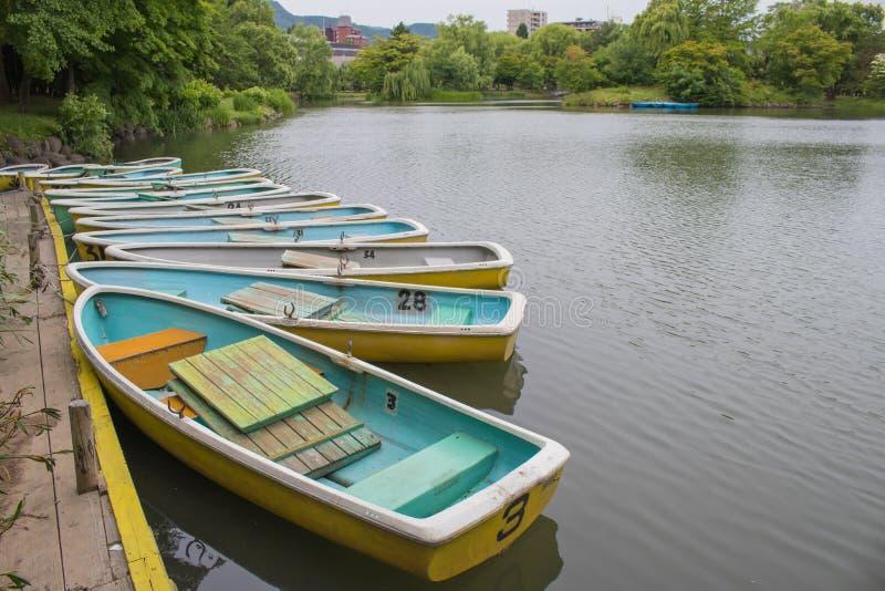 Rząd drewniany rowboat lub sampan unosi się na jezioro porcie w chmurnym dniu prawie przy Nakajima parkiem Koen, Sapporo miasto, obraz royalty free