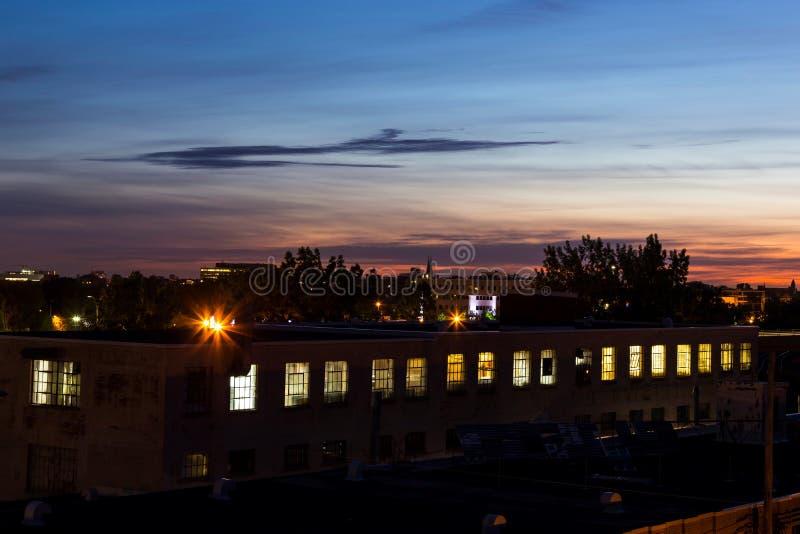Rząd iluminujący okno w historia z pierwszych stron stary przemysłowy budynek przy wschodem słońca obrazy stock
