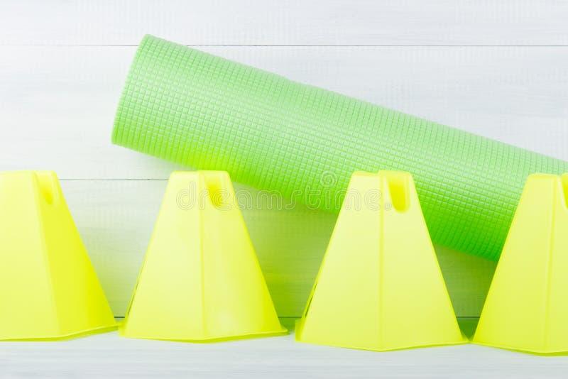 Rząd kolor żółty konusuje i sport zieleni mata dla sprawności fizycznej, na szarym tle zdjęcie royalty free