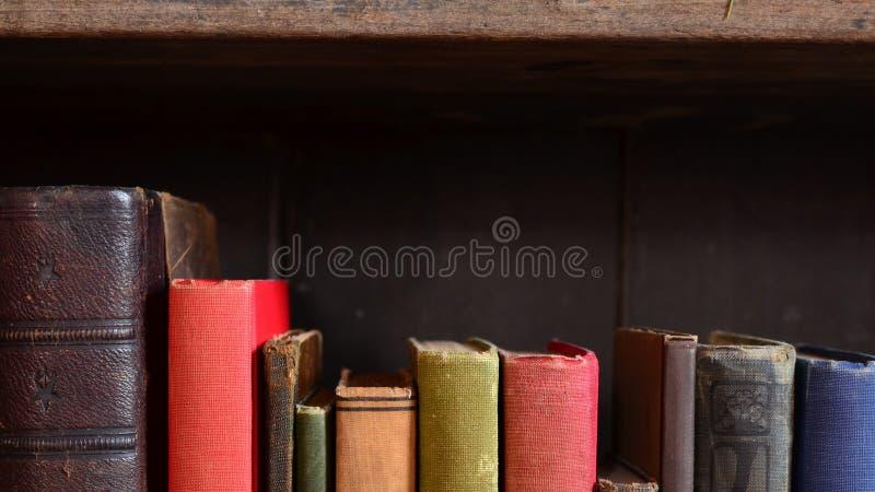 Rząd kolorowy rocznik rezerwuje na starym półka na książki zdjęcia royalty free