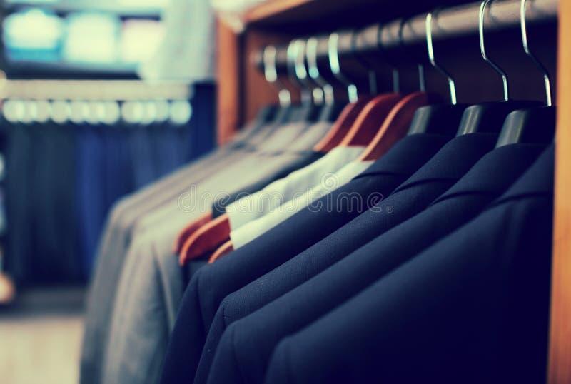 Rząd kurtki na wieszakach w mężczyzna sklepie odzieżowym fotografia stock