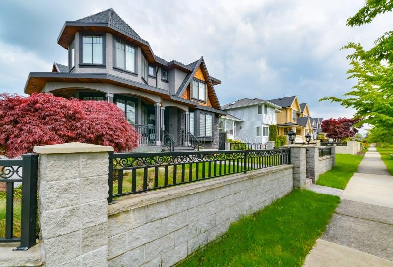 Rząd mieszkaniowi domy z betonową drogą przemian wzdłuż frontowego jarda Metalu ogrodzenie przed mieszkaniowym domem obrazy royalty free
