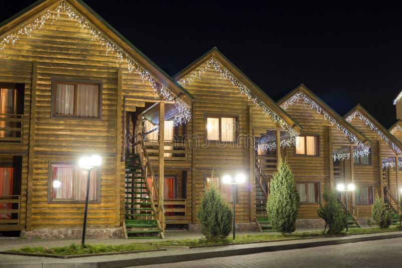 Rząd nowi jednopiętrowi ekologiczni drewniani wygodni dekorujący chałupa hotele na czystej iluminującej ulicie pod ciemnym nocnym zdjęcia royalty free