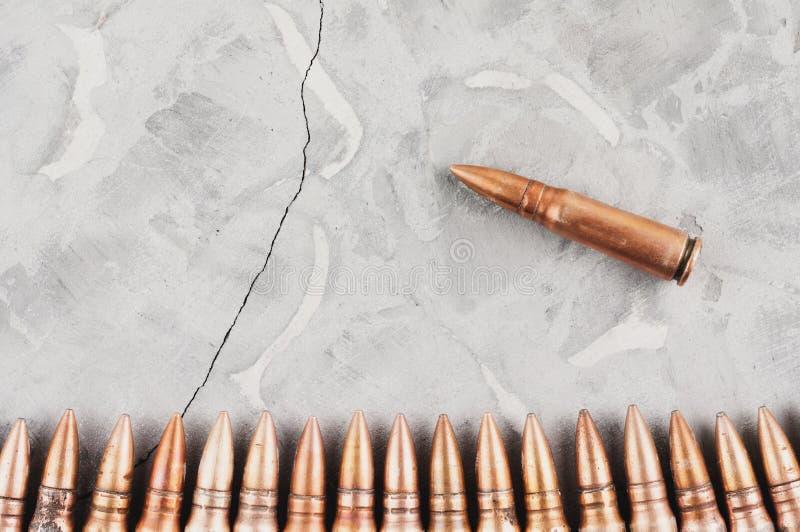 Rząd pociski i pojedynczy pocisk na popielatym łamającym betonie zdjęcia stock