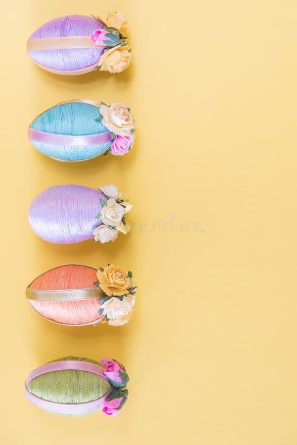 Rząd roczników style barwiący Wielkanocni jajka na sprzedającym żółtym tle obraz stock
