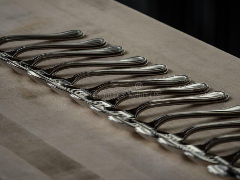 Rząd srebro łyżki na drewnianym stole i rozwidlenia obrazy stock
