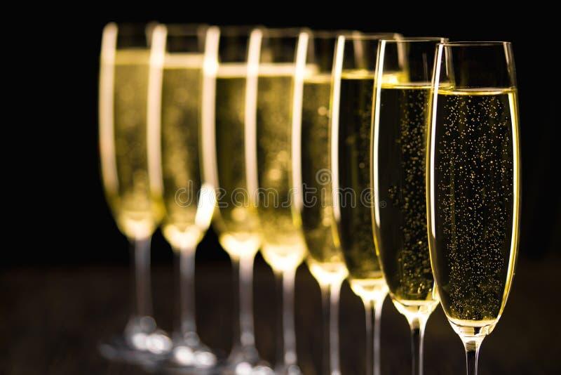 Rząd szampańscy szkła na czarnym tle Selekcyjny foc zdjęcia royalty free