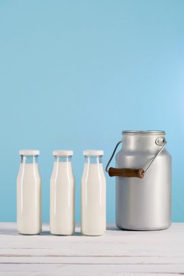 Rząd szklane butelki z mlekiem na tabletop z puszką fotografia stock