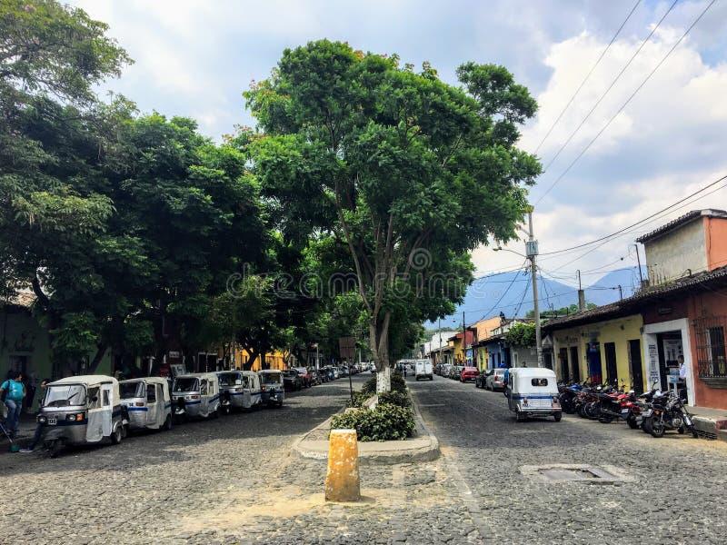 Rząd tuków tuks parkujący wzdłuż szerokiego brukowa bulwaru Antigua, Gwatemala zdjęcia stock