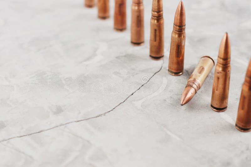 Rząd wiele metali pociski i jeden spadać pocisk na popielatym łamającym betonie obraz stock