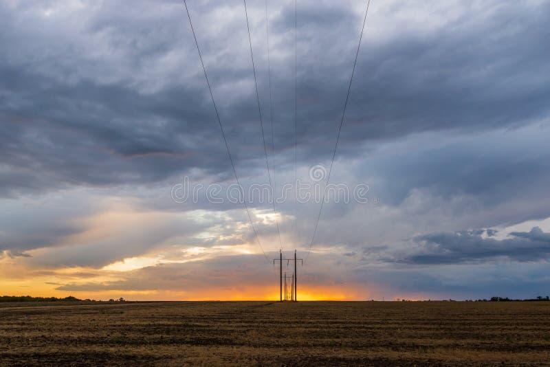 Rząd wysokiego woltażu elektryczne linie energetyczne przylega horyzont w inaczej szerokim, szeroko otwarty wiejskim krajobrazie  zdjęcie stock