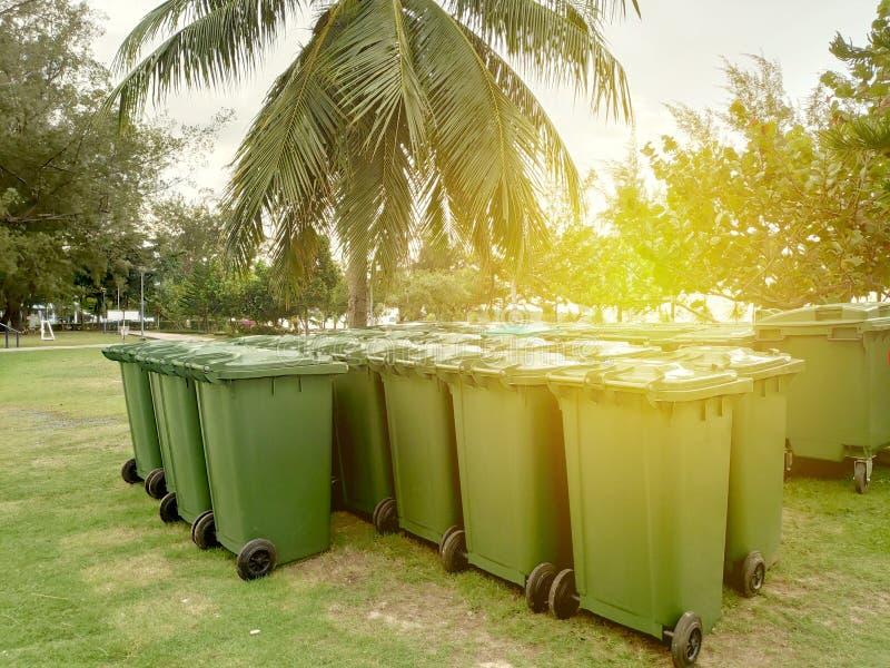 Rząd zielony kosz na śmiecie z słońce racą Zanieczyszczenia pojęcie fotografia stock