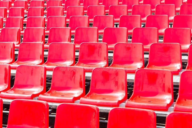 Rzędy opróżniają czerwonych plastikowych siedzenia w stadium obraz stock