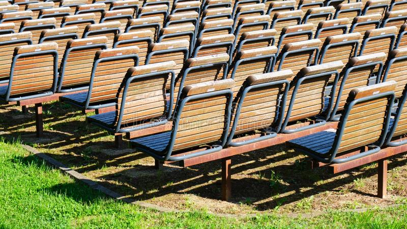 Rzędy puści drewniani krzesła, uszeregowywam outside w słońcu na zielonej trawie, Pojęcie dla wydarzeń, zgromadzenia, pokazuje fotografia royalty free
