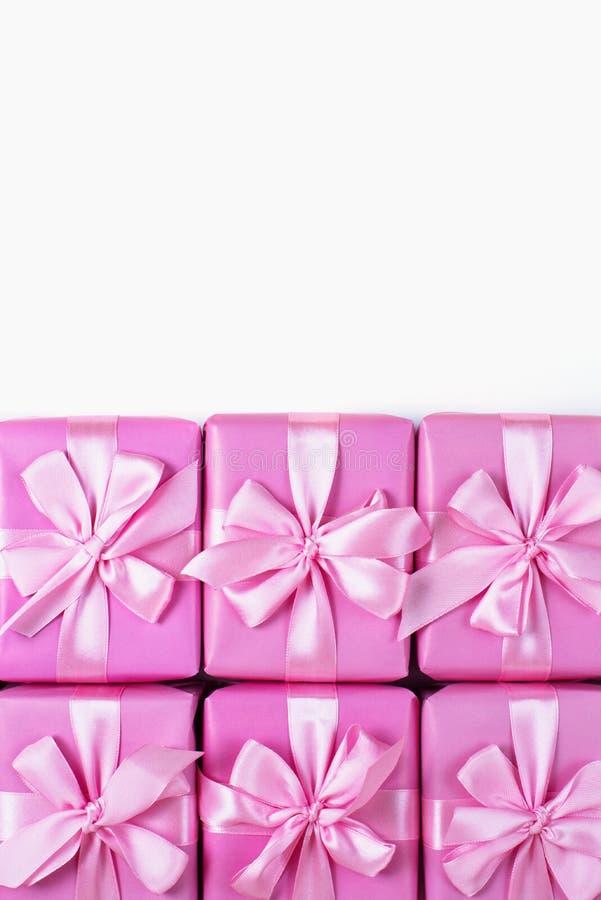Rzędy pudełka sześć z prezent dekoraci łęku menchii A tasiemkowym atłasowym odgórnym widokiem nieatutowym mieszkanie obrazy stock