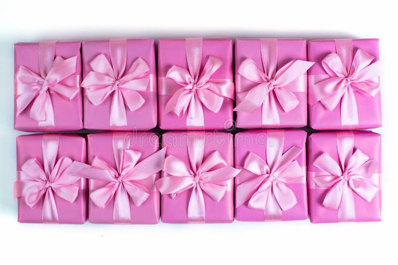 Rzędy pudełka z prezent dekoraci tasiemkowym atłasowym łękiem różowią A odgórnego widok nieatutowego mieszkanie zdjęcia stock