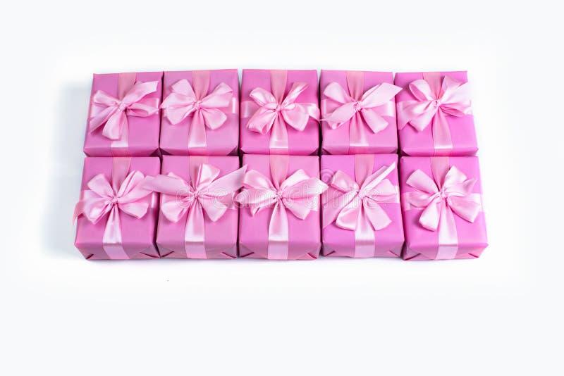 Rzędy pudełka z prezent dekoraci tasiemkowym atłasowym łękiem różowią A odgórnego widok nieatutowego mieszkanie obrazy stock